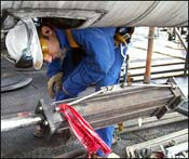 Field service technician inspecting a hydraulic snubber